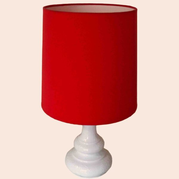 Eine große Tischlampe mit auffälligem, rotem Schirm und Wallendorfer Porzellan-Fuß in Weiß
